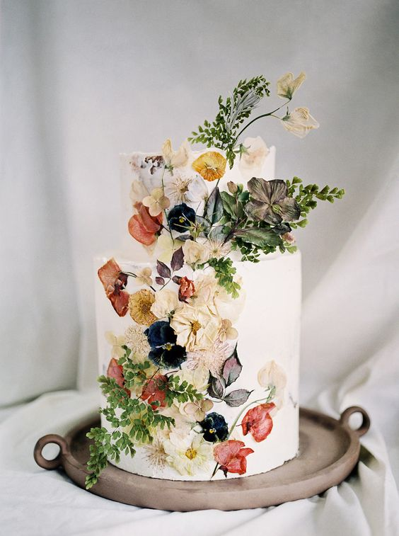a-beautiful-wedding-cake-inspired-by-Dutch-Masters-a-white-wedding-cake-with-pressed-edible-flowers-and-leaves-is-very-chic